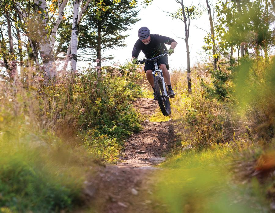 Hansi Johnson mountain biking on a trail through the woods.