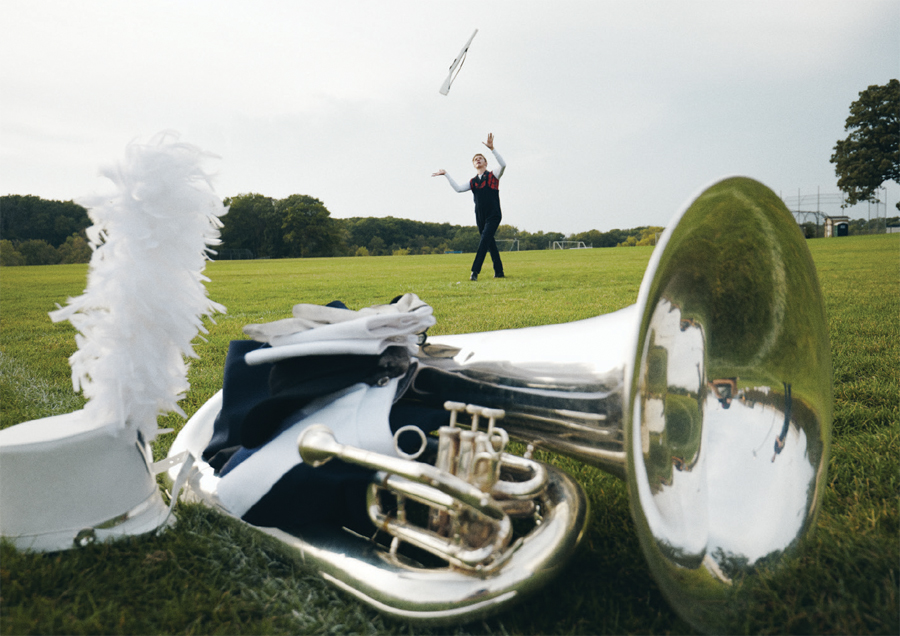 A tuba and marching band hat with plume rest in the foreground on a football field while a color guard member practices throwing a rifle in the background.