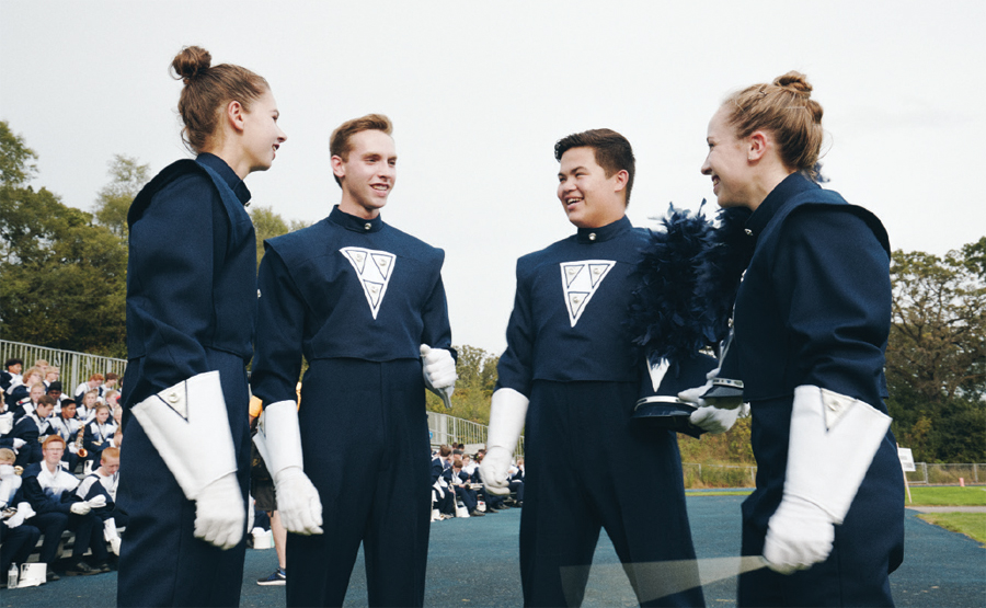 A group of marching band members standing in a circle and hanging out before the performance.