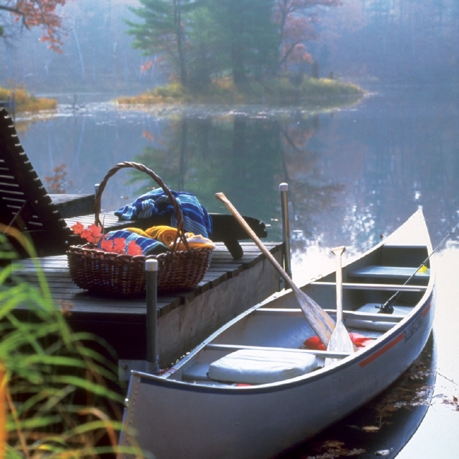 A canoe along with equipment sitting by a dock at Canoe Bay.