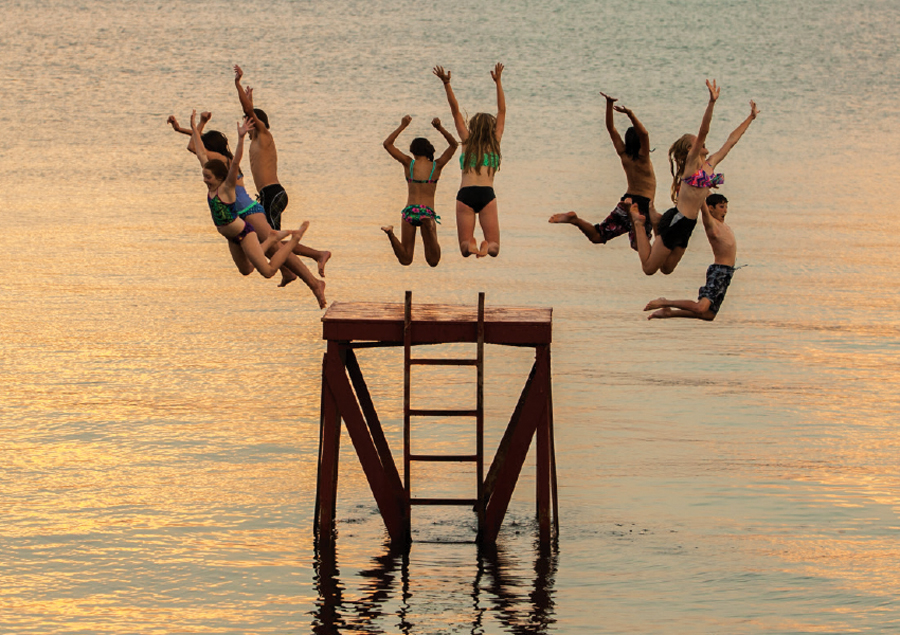 Kids jumping off a platform into a lake at Fair Hills Resort.