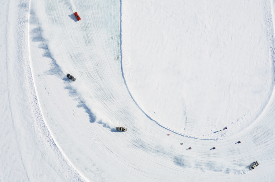 An overhead view of cars racing on a frozen lake.