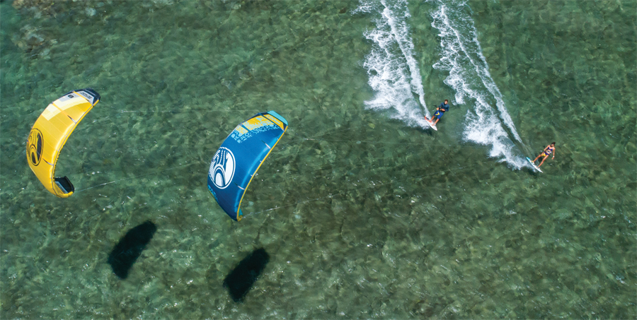 An aerial view of people kiteboarding.
