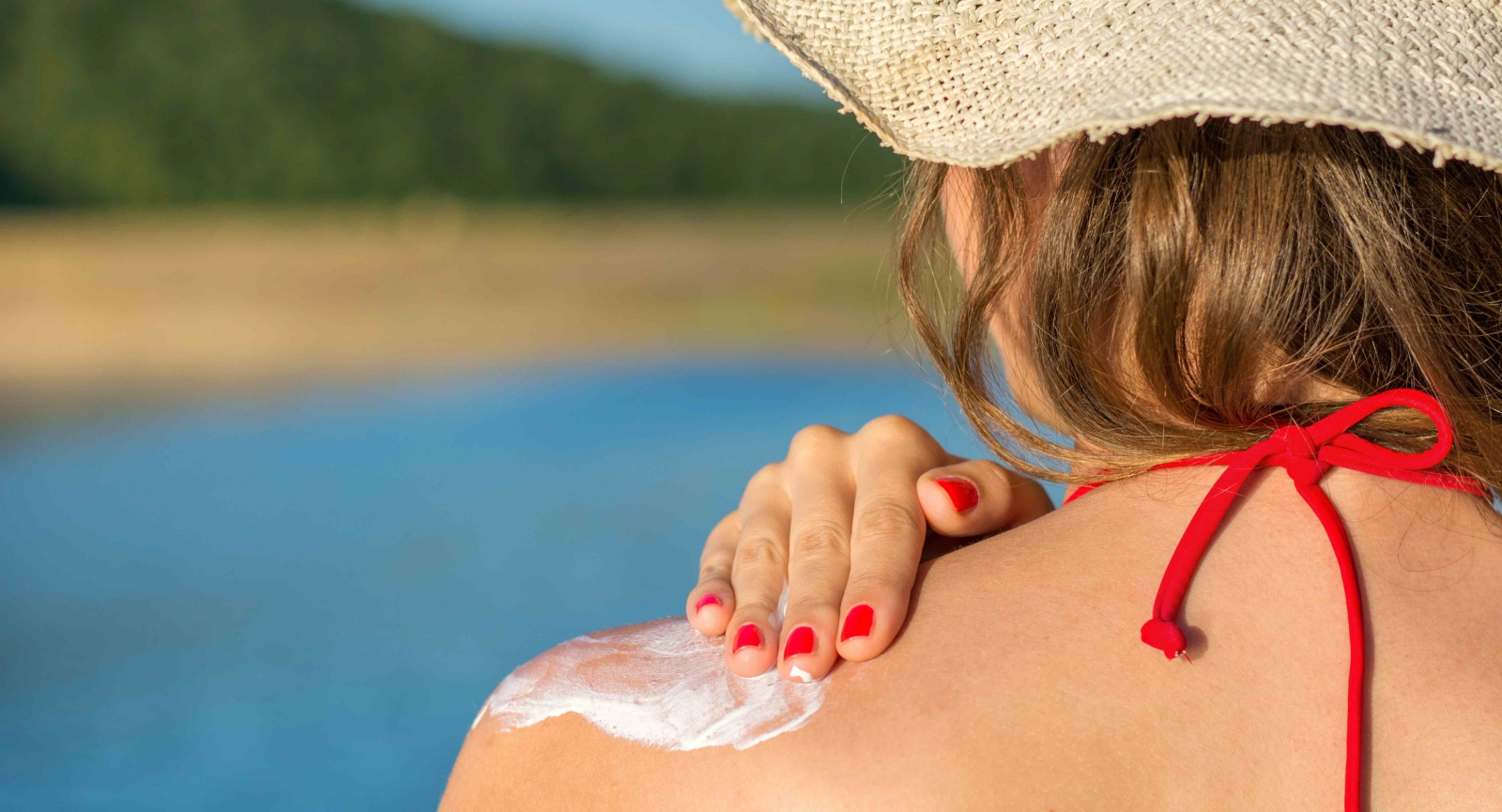 Photo by creativefamily/Fotolia. A woman putting sunscreen on her shoulder on the beach.