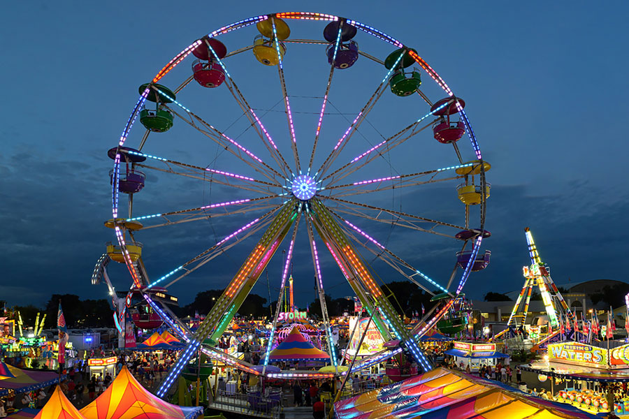 A picture of the ferris wheel and other Midway rides at night at the Minnesota State Fair.