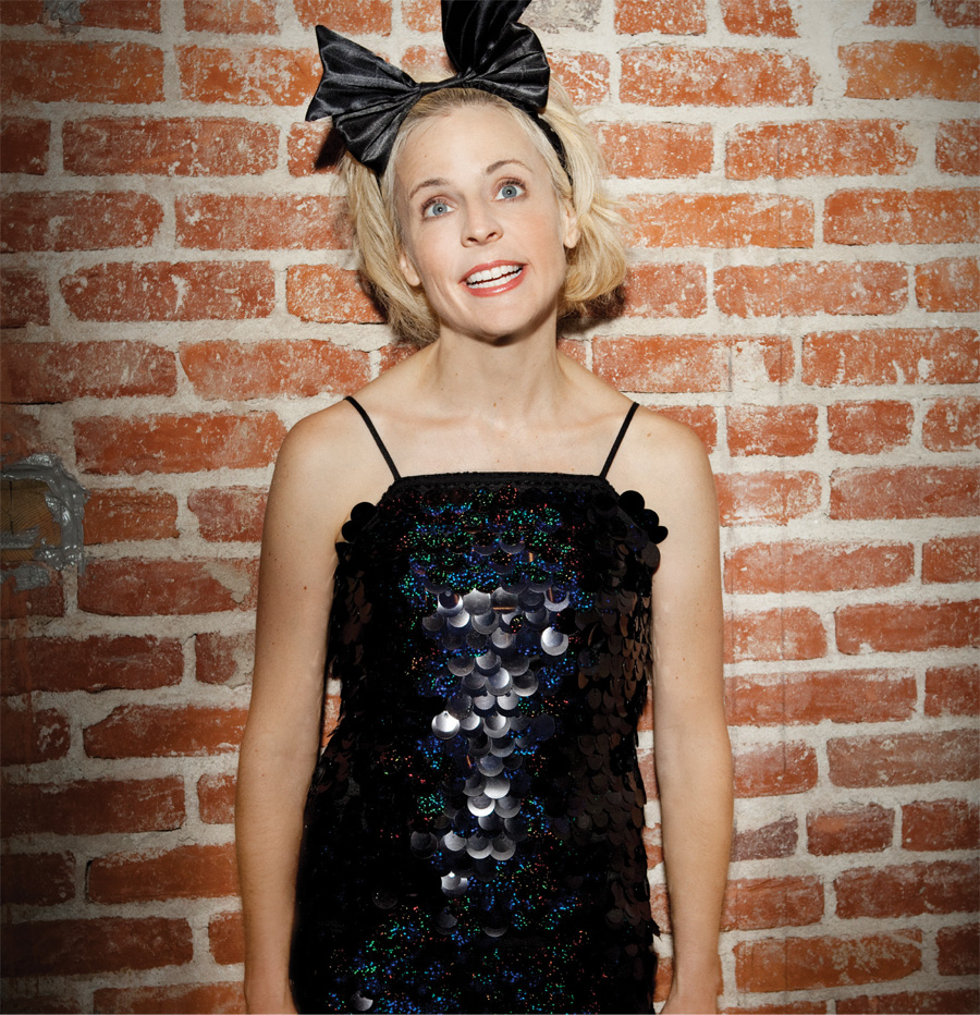 A portrait of Maria Bamford wearing a black dress and bow against a brick wall.