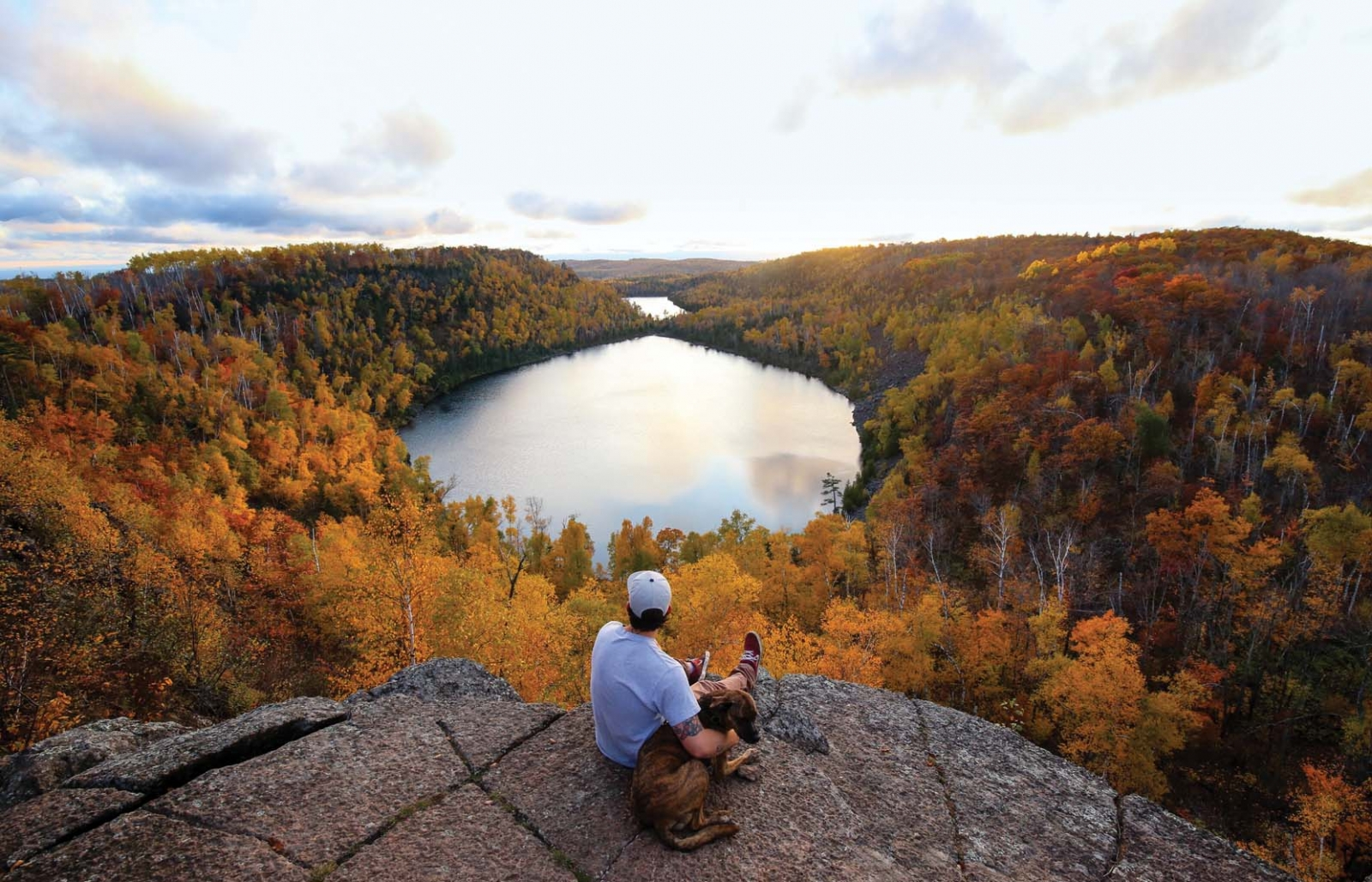 A man sitting on an overlook with a lake and trees in the background.
