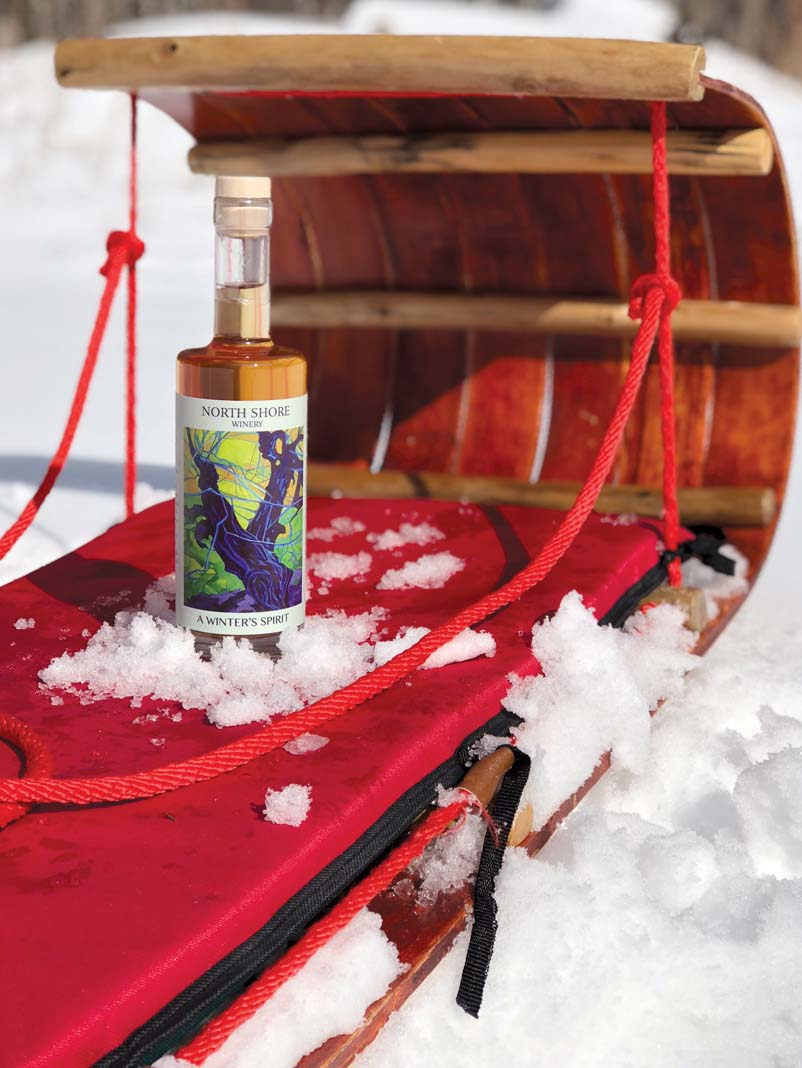 A bottle of wine from North Shore Winery sitting on a sled outdoors.