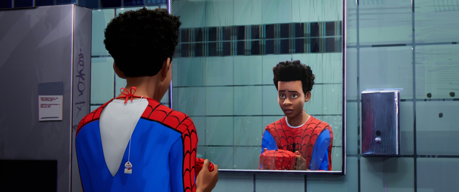 A shot of character Miles Morales staring at himself in the mirror, holding the Spiderman mask, in Spiderman: Into the Spider-Verse.