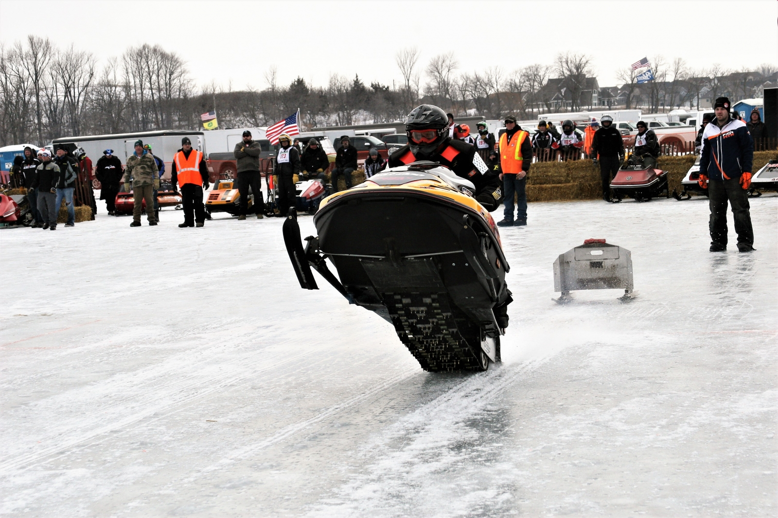 """A snowmobile driver lifting up the front of the sled in a """"wheelie"""" at the Waconia Ride-In. Courtesy Waconia Ride-In."""
