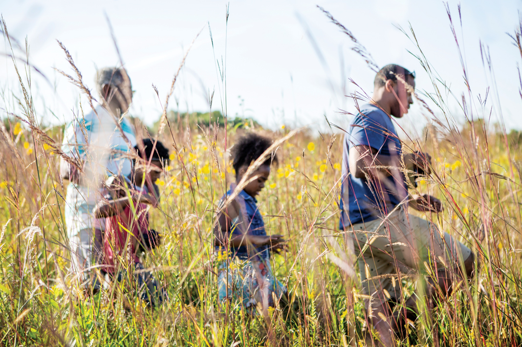 A family walks through the tall prairie grass in Blue Mounds State park
