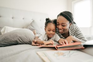 Mom and toddler reading a book in bed