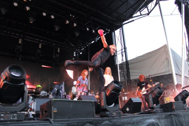 The National performs at Rock the Garden, with lead singer Matt Berninger balancing on one foot and his drink spilling out of his red solo cup on to him.