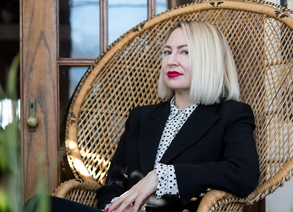 Jahna Peloquin sitting in a chair, with a dotted collared shirt and a black blazer