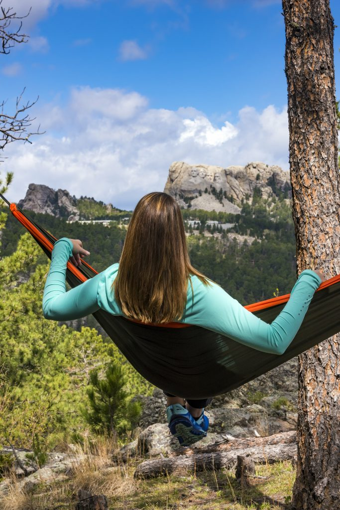 Girl in hammock looking out at view of Mount Rushmore