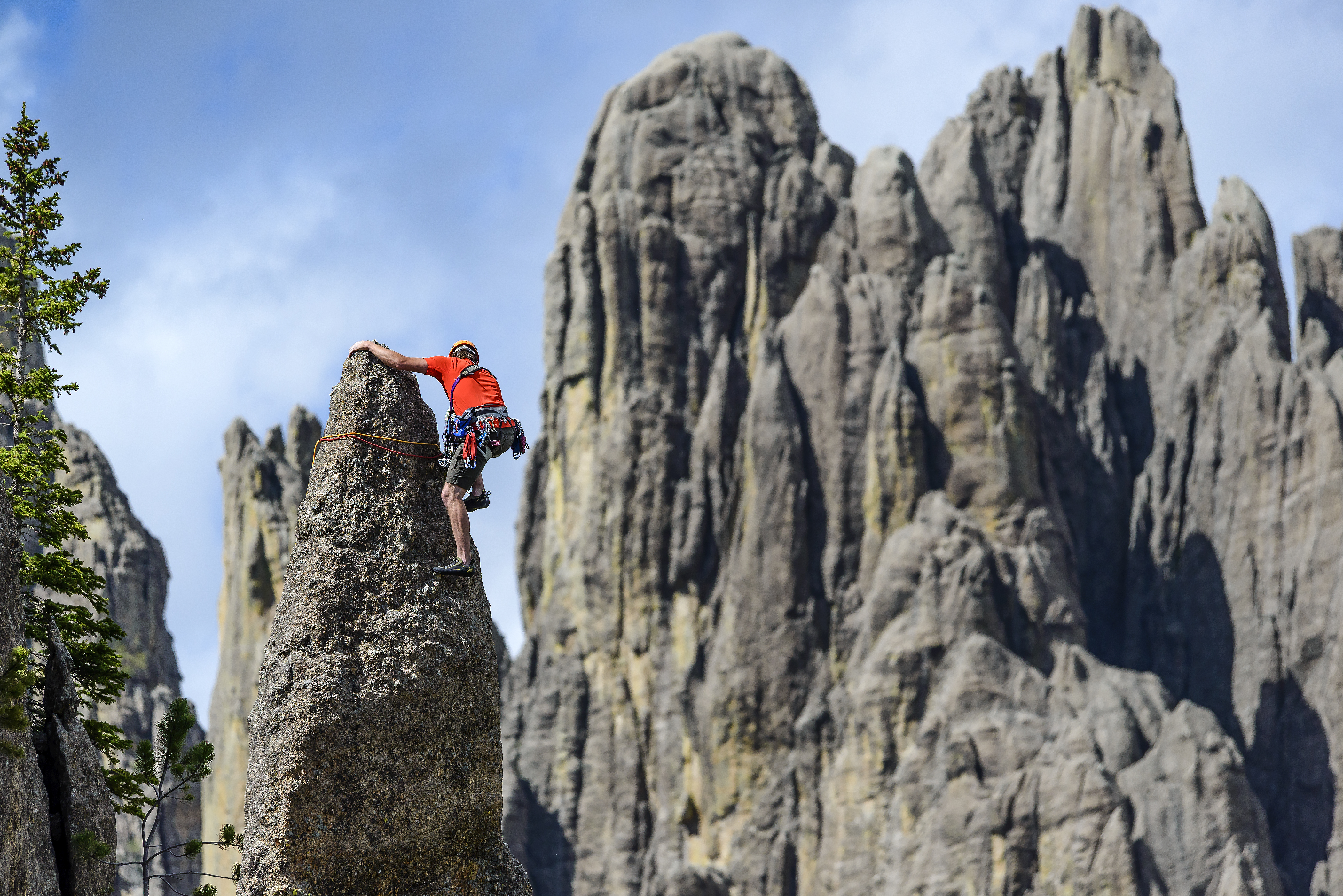 """Rock climber at the top of a """"needle"""" in South Dakota with mountains in background"""