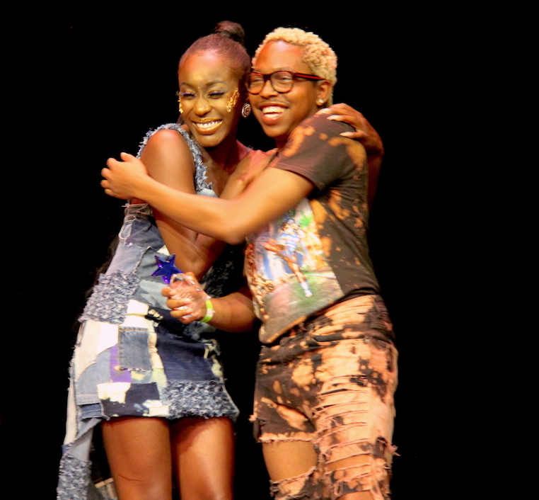 Model Toneh Gaypia and designer Kendall Ray hug upon hearing that they took third place at DesignICON 2
