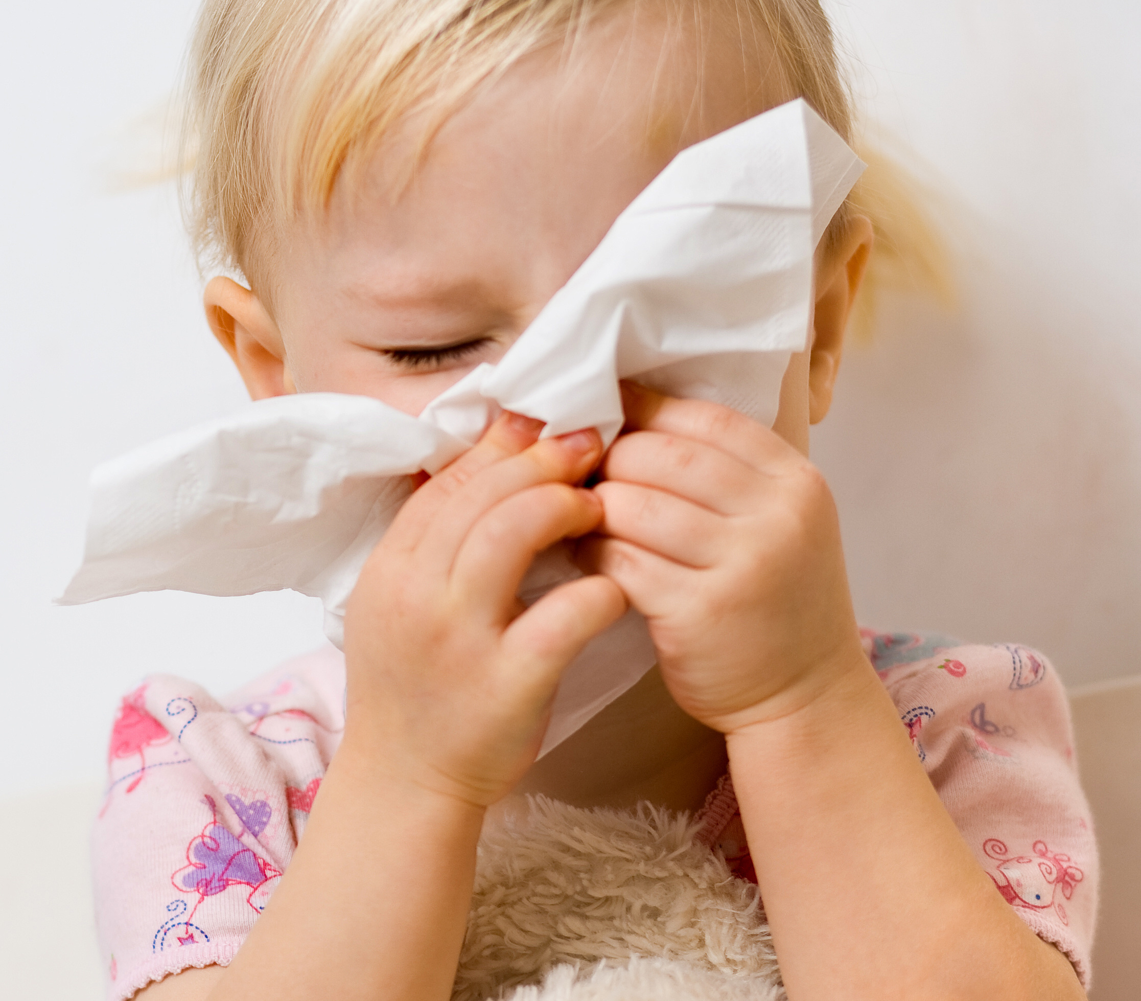 Little girl blows her nose into a tissue