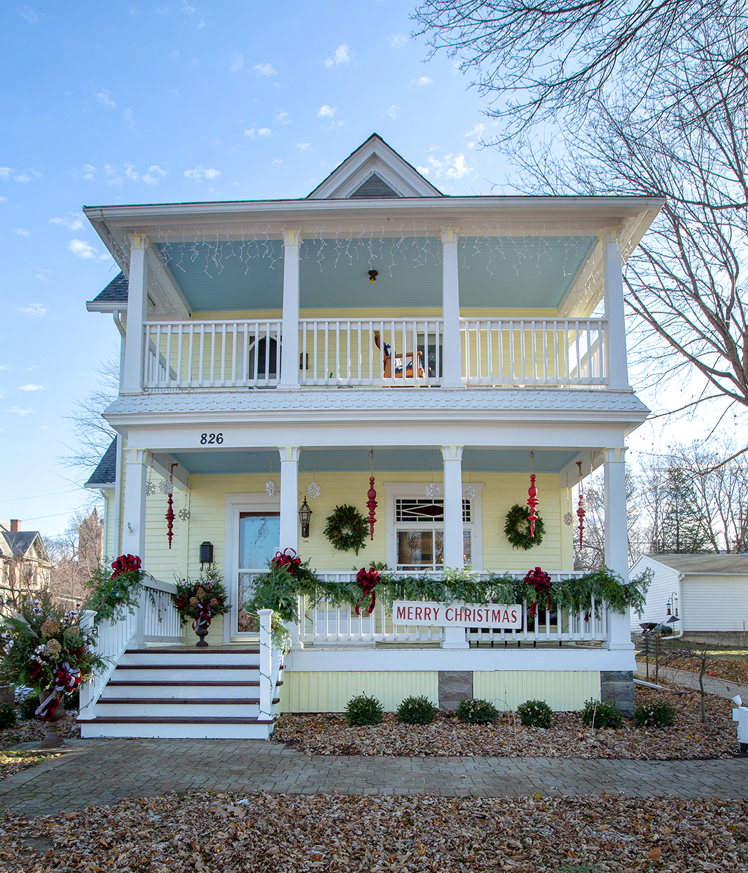 A two-story light yellow home decorated with holiday garland and wreaths.