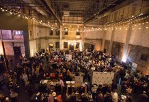 An event venue full of people visiting vendor booths