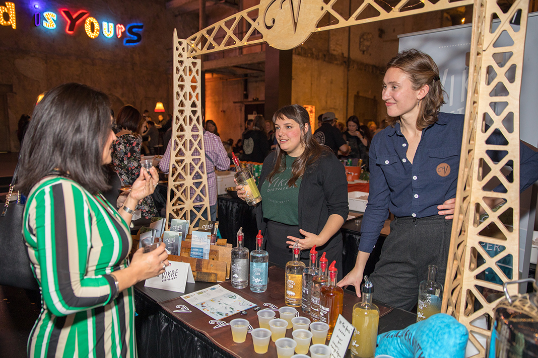 Two women who work for a Vikre Distillery mingle with an event attendee