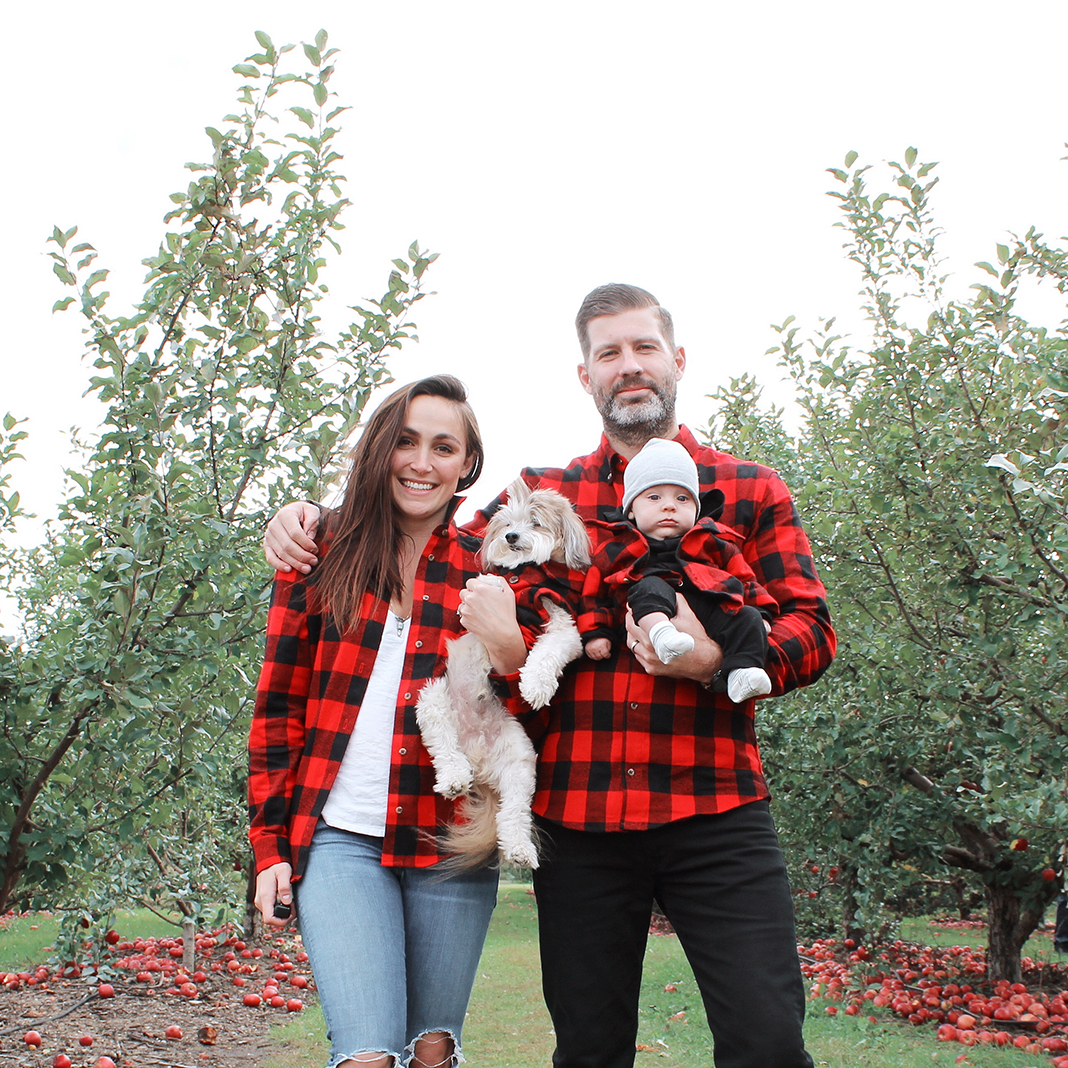 A caucasian family and dog in matching red and black buffalo plaid shirts.