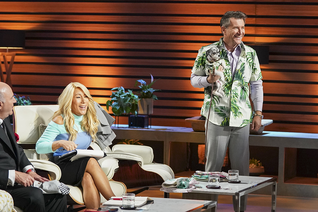 Shark Tank's Robert Herjavec tries on one of Dog Threads' Hawaiian shirts to match one of the dogs brought on set.