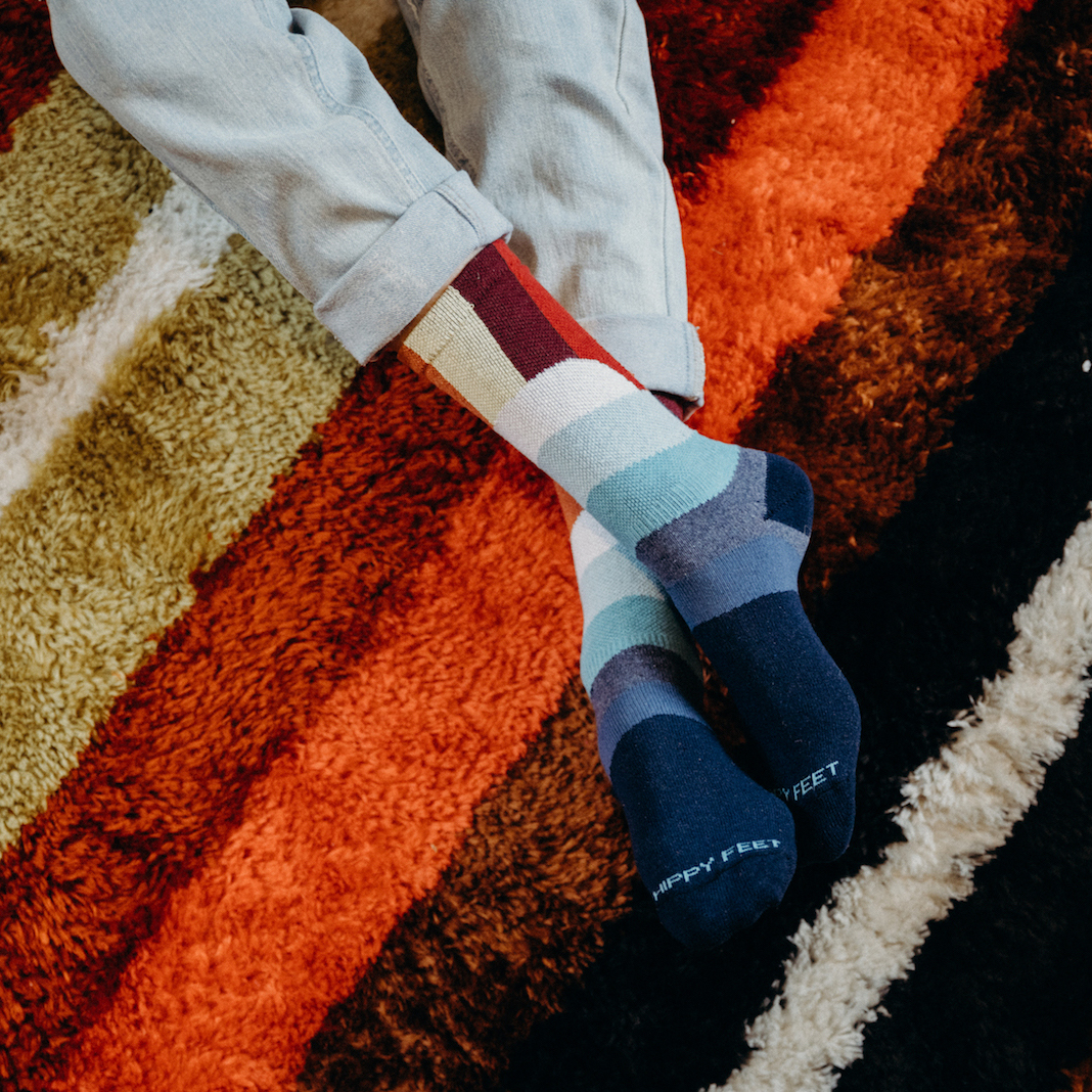 Someone's crossed legs on top of a striped rug in colorful socks made by Hippy Feet.