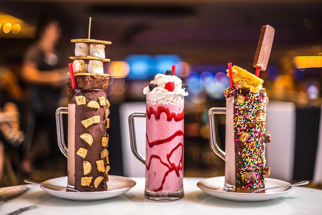 Three milkshakes with sugary toppings