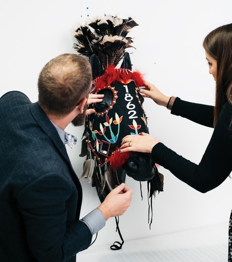 "MNHS's Ben Gessner and Rita Walaszek prepare ""1862 Sung Ite Ha"" horse mask by James Star Comes Ou (Oglala Lakota)"