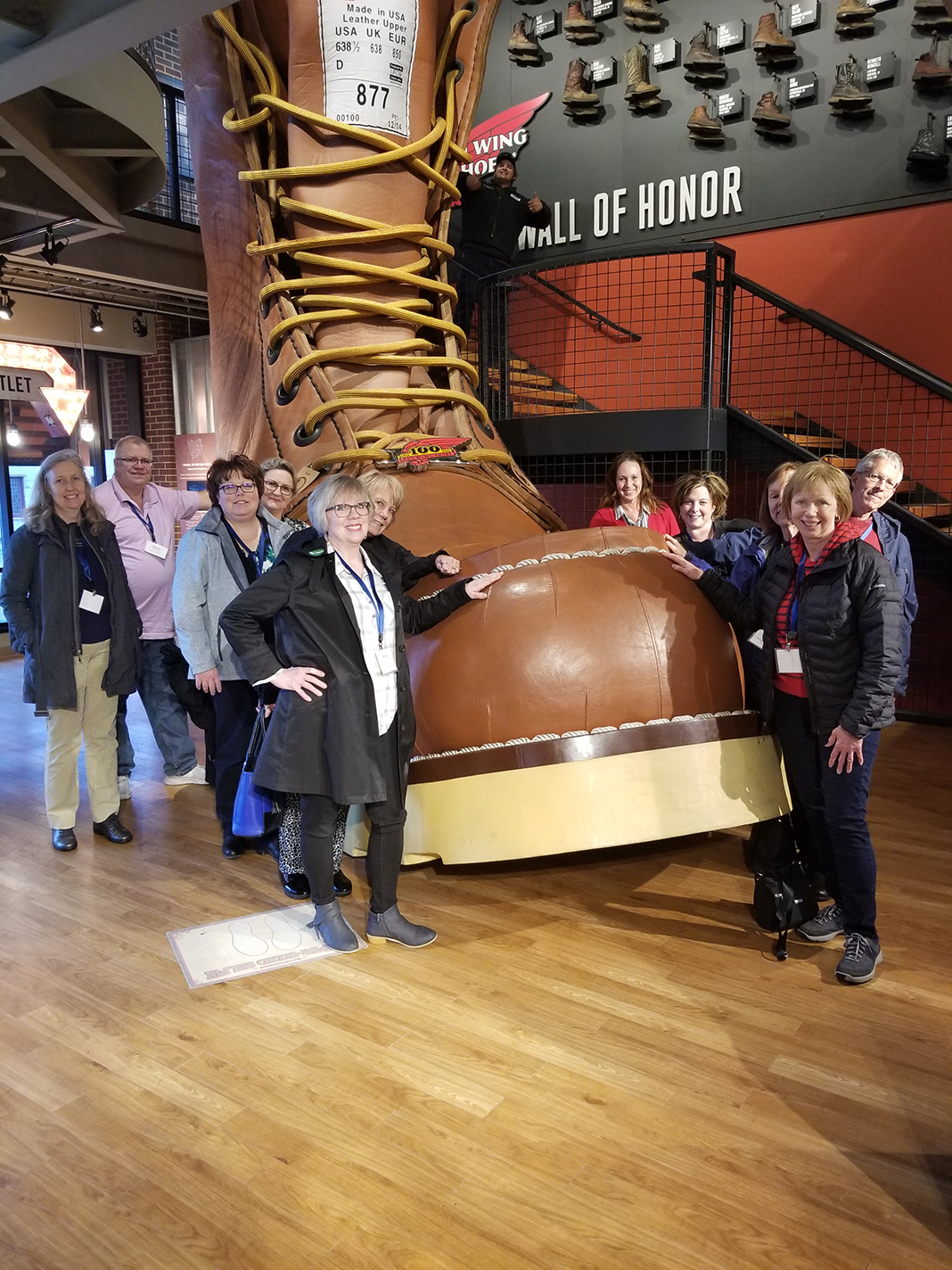 A group of tourists posing for a photo in front of the World's Largest Boot at The Red Wing Shoe Museum.