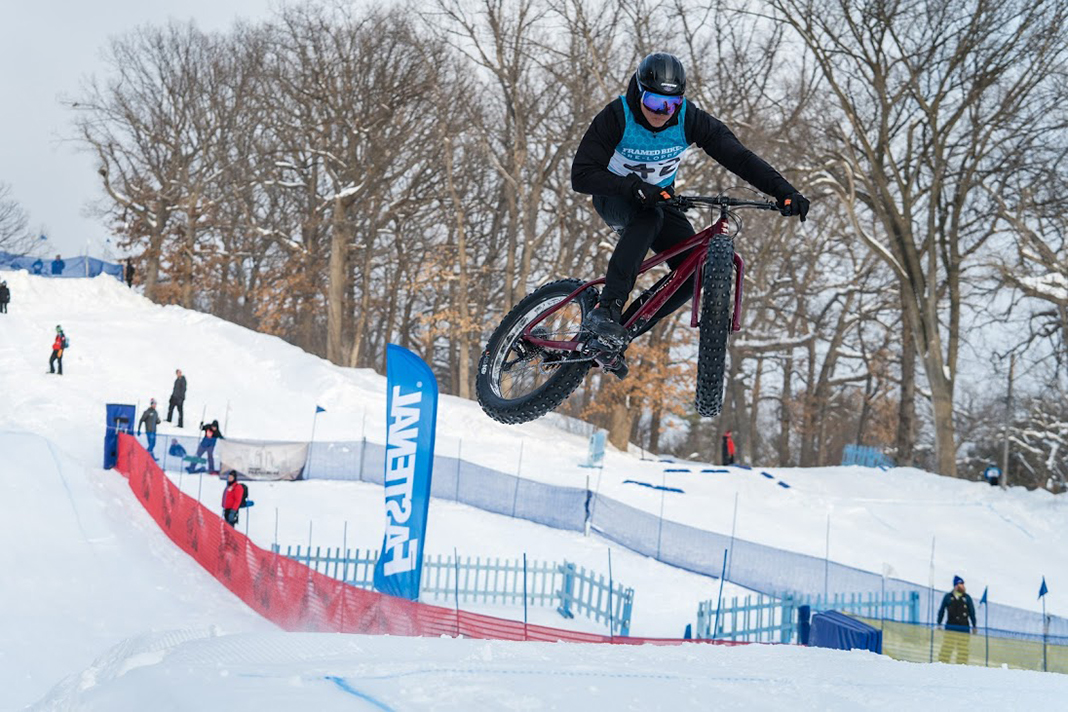 A man in mid-air on a fat tire bike at the Fastenal Parallel 45 Winter Festival