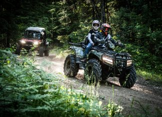 Two people driving an ATV with another ATV in the background