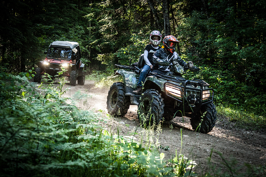 Two people driving an ATV through the woods with another ATV in the background