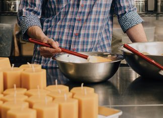 Worker B co-founder Michael Sedlacek stirs locally produced honey at his production facility in northeast Minneapolis, behind stacks of beeswax candles