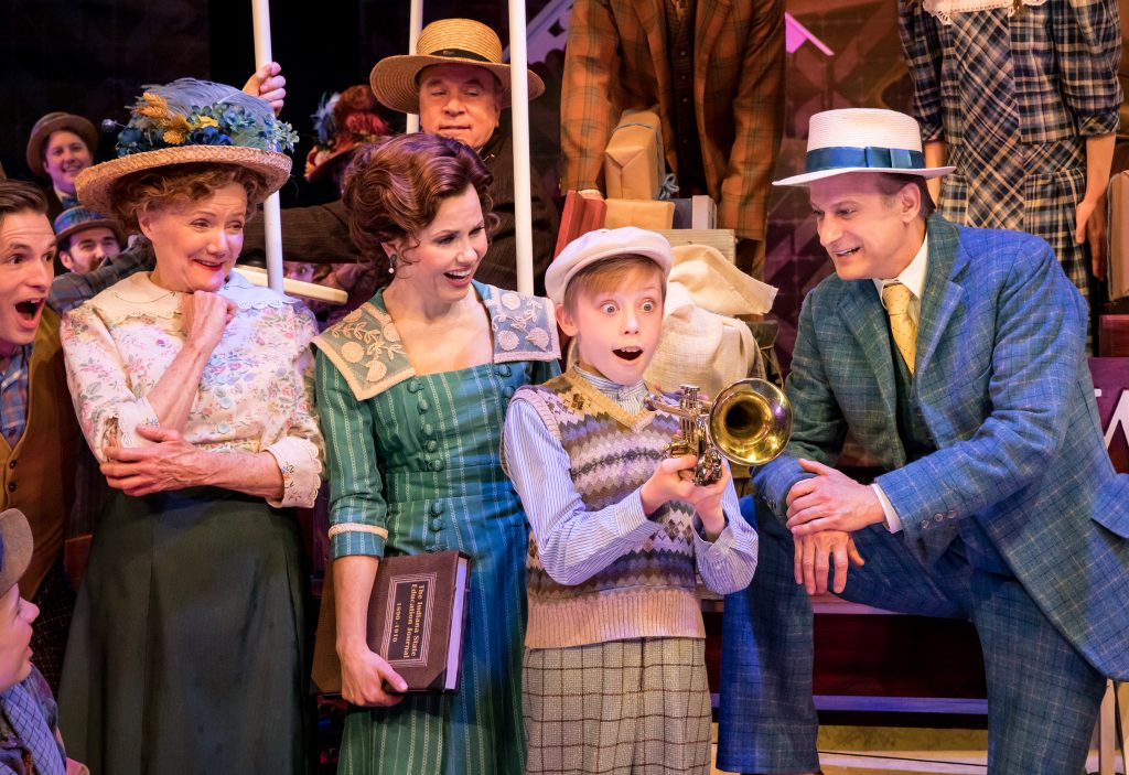 In the foreground, from left to right: Peggy O'Connell as Mrs. Paroo, Ann Michels as Marian Paroo, Hugo Mulaney as Winthrop Paroo, and Michael Gruber as Harold Hill. Photo by Dan Norman, 2020, at Chanhassen Dinner Theatres' The Music Man.