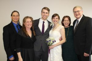 Sam and Emma Johnson with their parents on their wedding day.