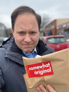 Jason DeRusha holds a takeout meal from Zettas on Eat Street
