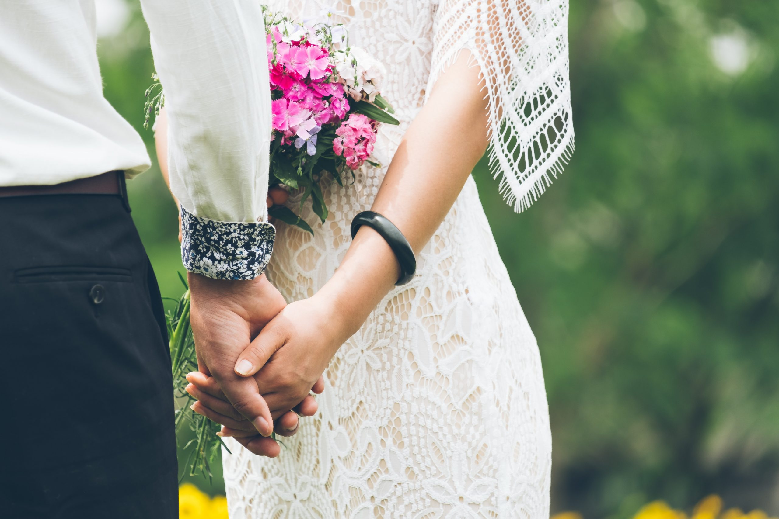 A wedding couple outside in the spring, holding hands.