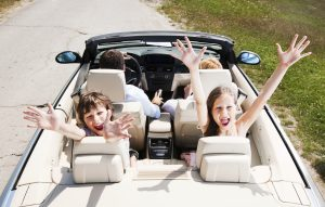 Happy family of four people sitting in their cabriolet car.