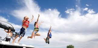 Kids jump off the back of a boat, enjoyed at Arrowwood Resort & Conference Center