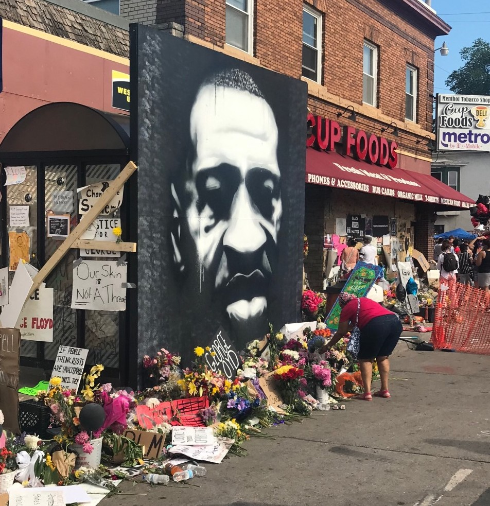 Visitors to George Floyd's memorial site place offerings before a large portrait