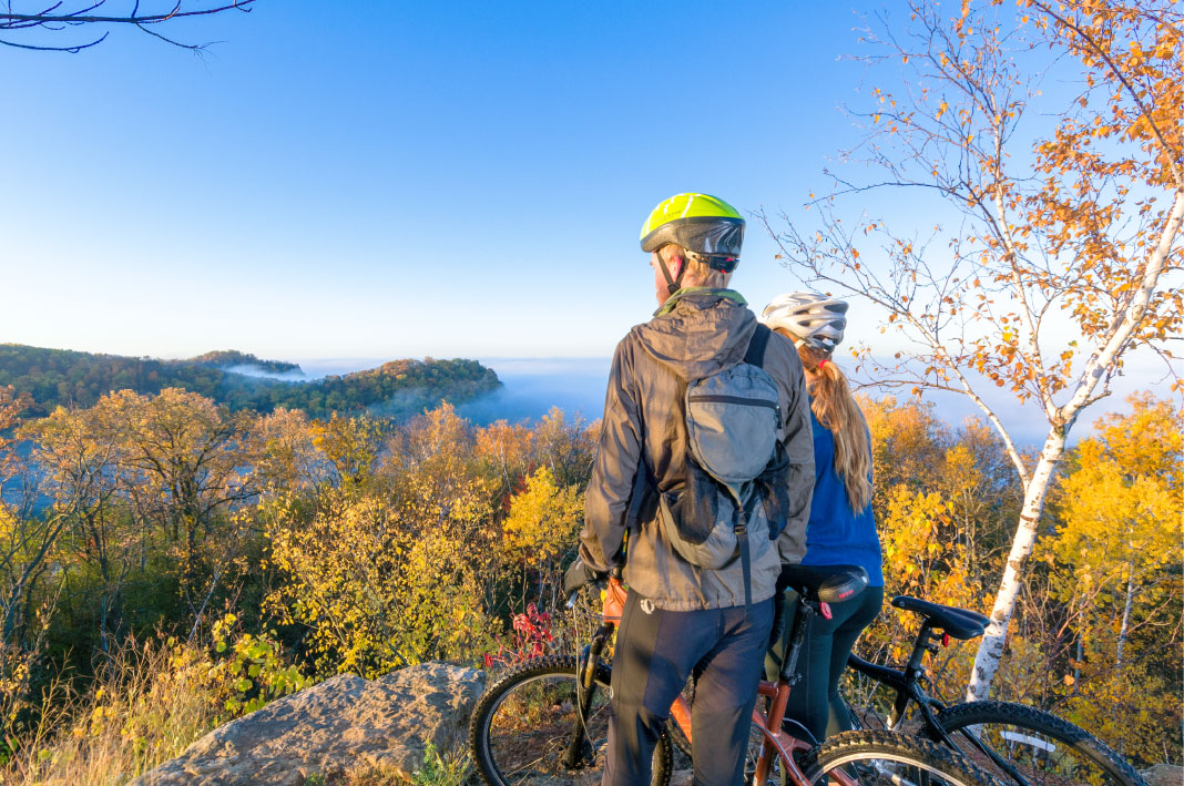 A couple standing next to bikes looking out at the fall foliage and a lake in La Crosse