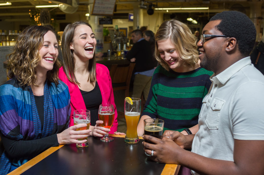Three women and a man sit a table holding beer at Pearl Street Brewery in La Crosse