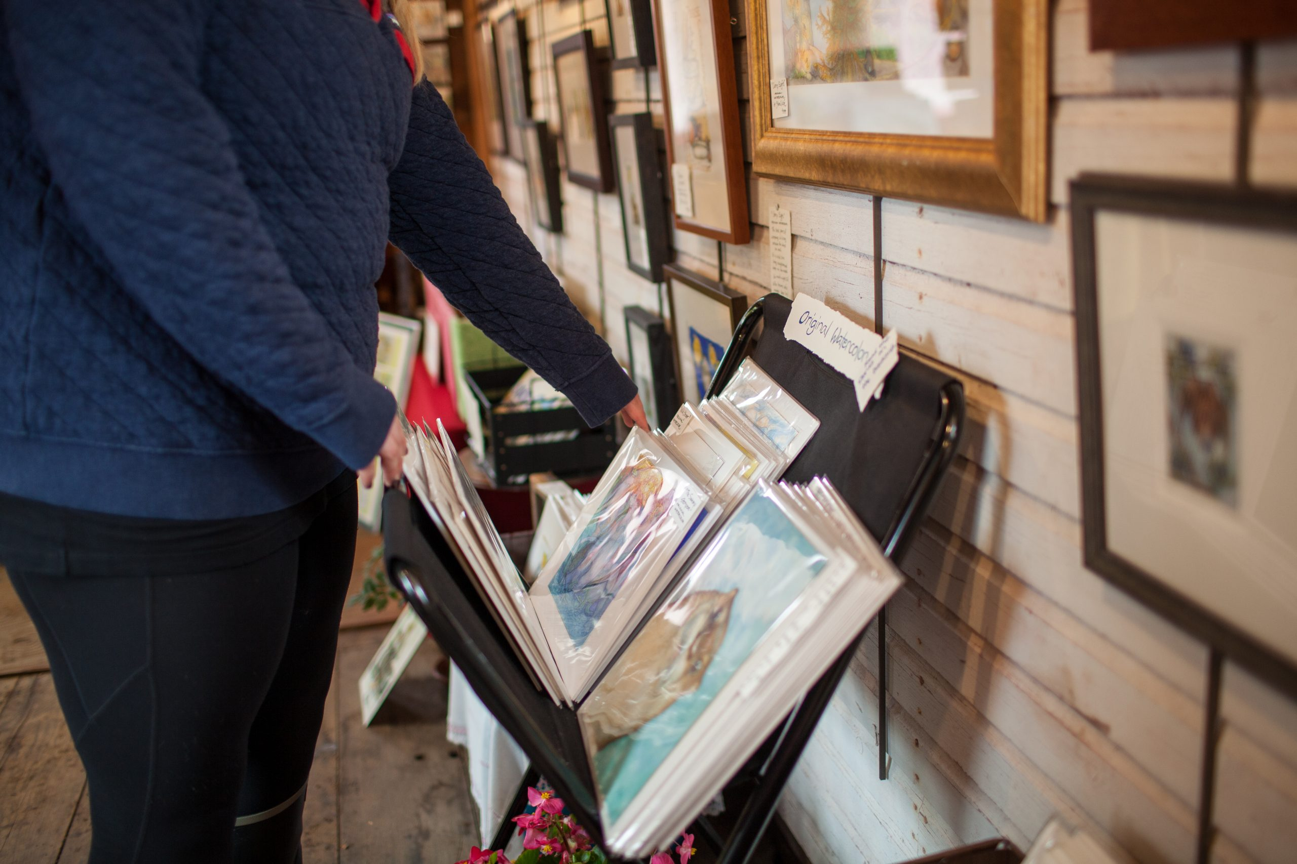 Woman looks through art prints at the Art Along the Lake Fall Studio Tour in Cook County