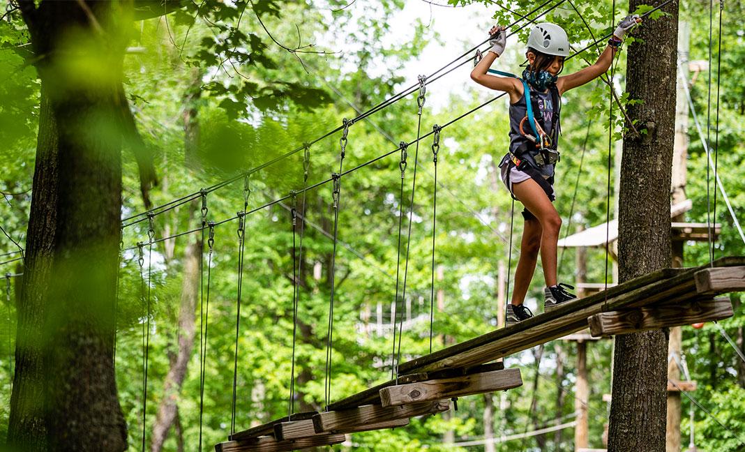 A girl walks across a suspended bridge on the Trollhaugen Kid's Course