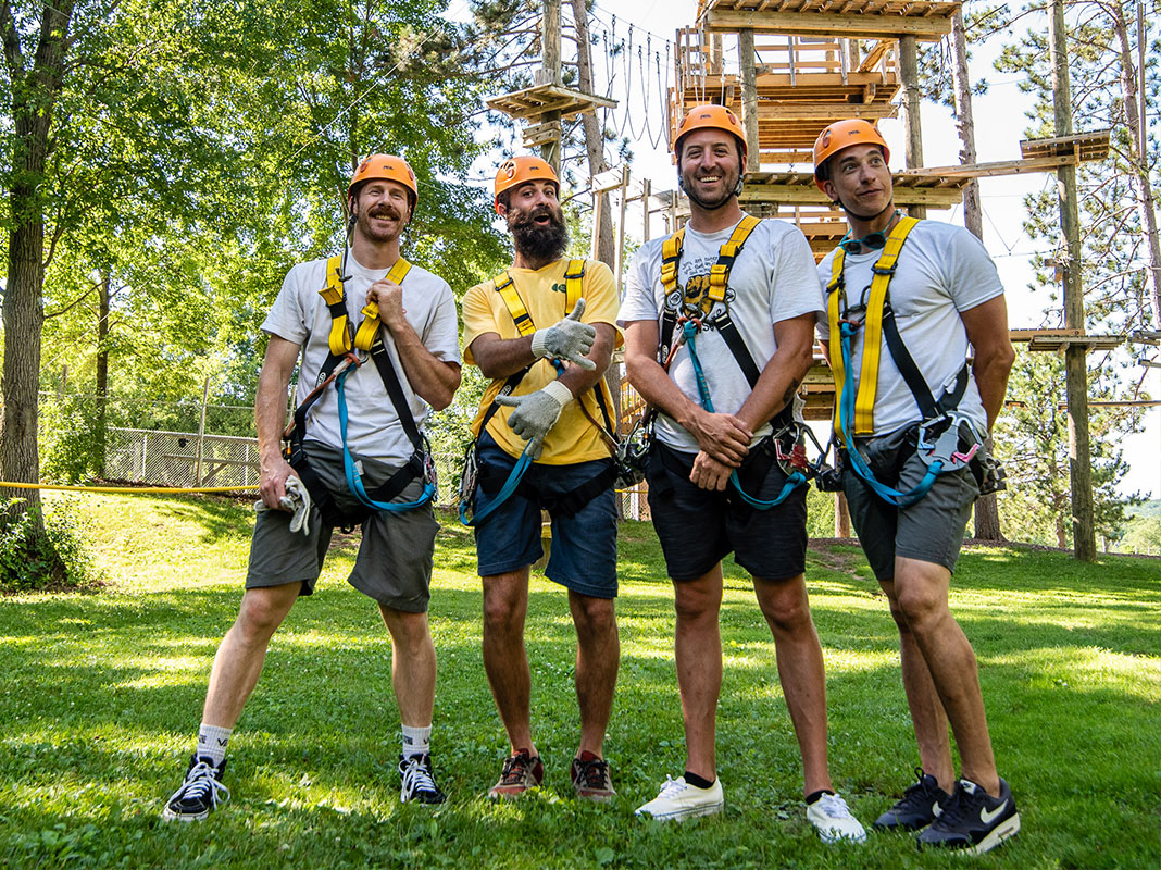 Four men wearing harnesses standing in front of Trollhaugen's high ropes course