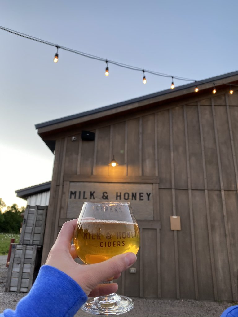 Person holding a glass of cider at Milk & Honey Ciders in St. Cloud