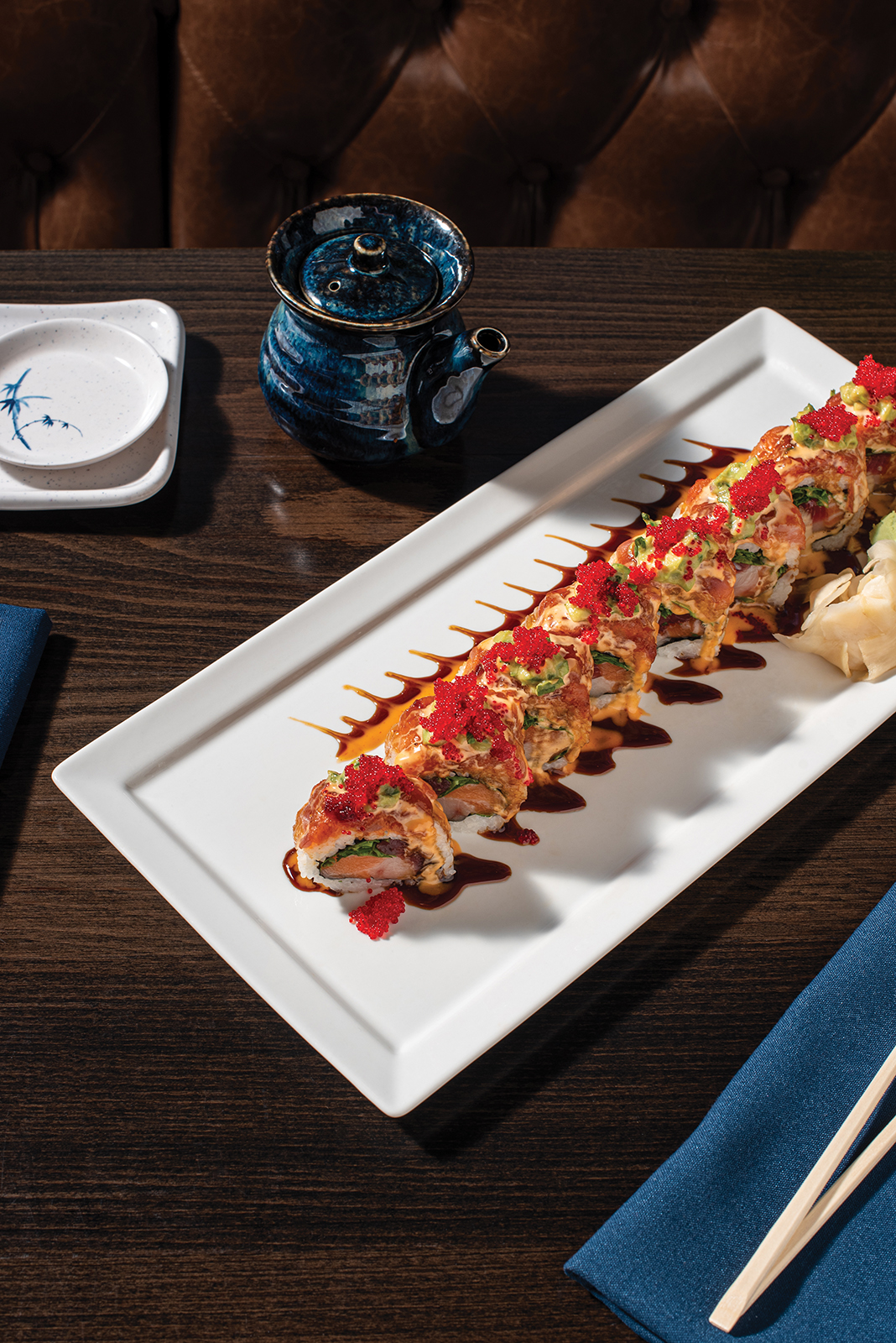 TITANIC ROLL: Yellowfin tuna, salmon, yellowtail, and cilantro wrapped with spicy tuna—topped with avocado salad, red tobiko, spicy mayo, and eel sauce