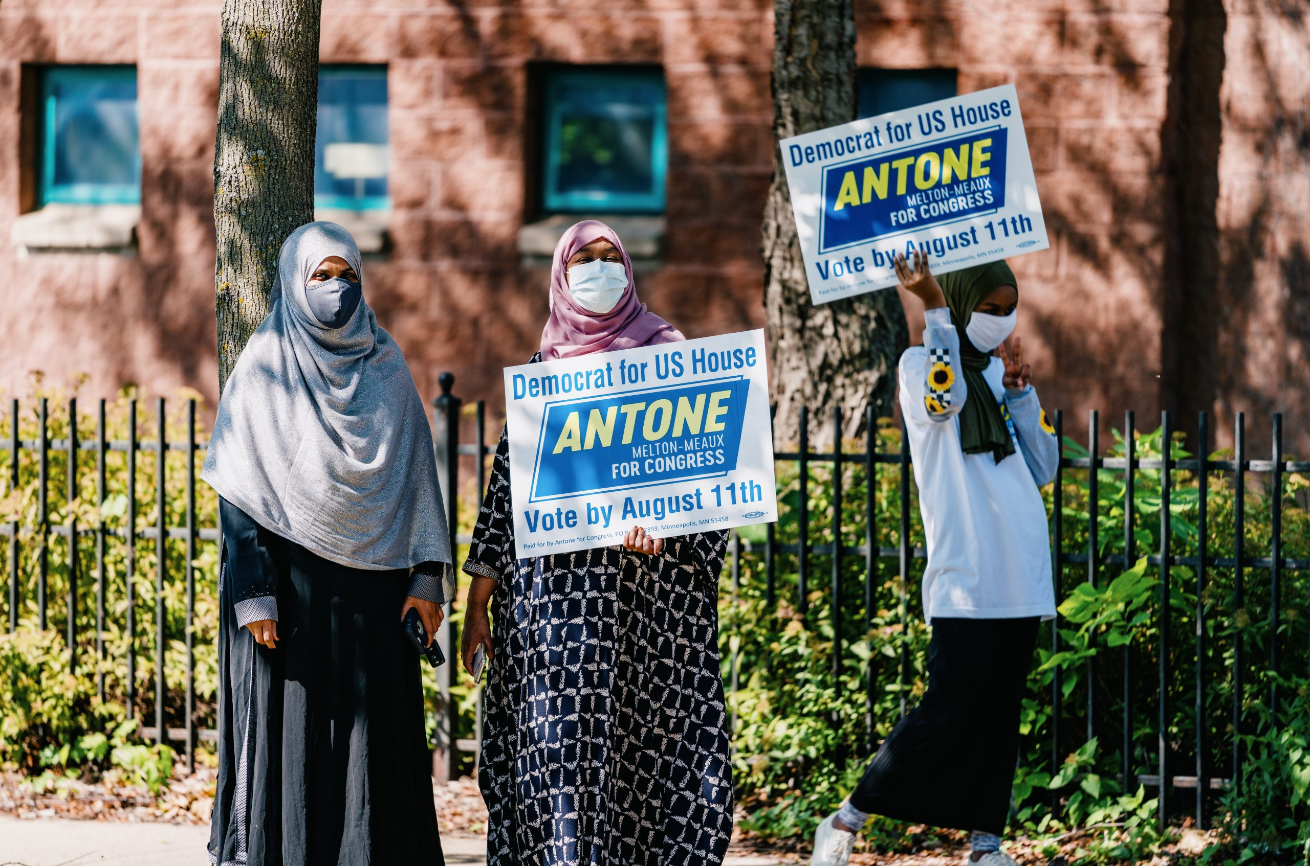 Three people wearing masks hold signs in support of Antone Melton-Meaux, a primary candidate for U.S. Representative